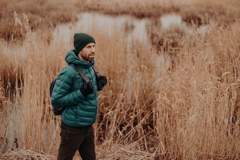 En longueur tiré du mâle actif habillé dans la veste et le chapeau chauds, porte le sac à dos, a la promenade dans la zone rurale photographie stock