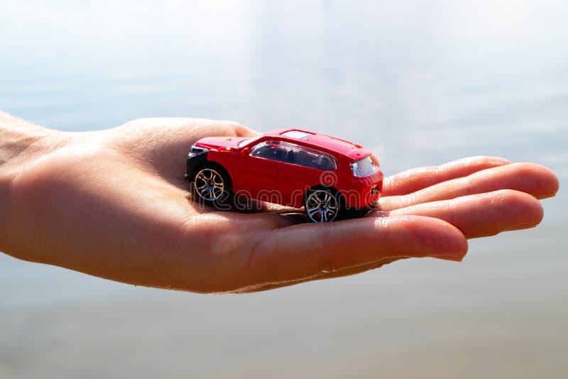 En los niños la palma es un coche rojo, el fondo fotos de archivo