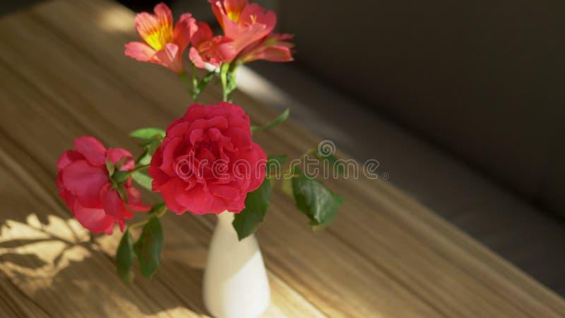 En ?lskv?rd bukett av rosor och freesia och skuggan av den p? tabellen som t?nds av solljus till och med gardinen royaltyfri bild