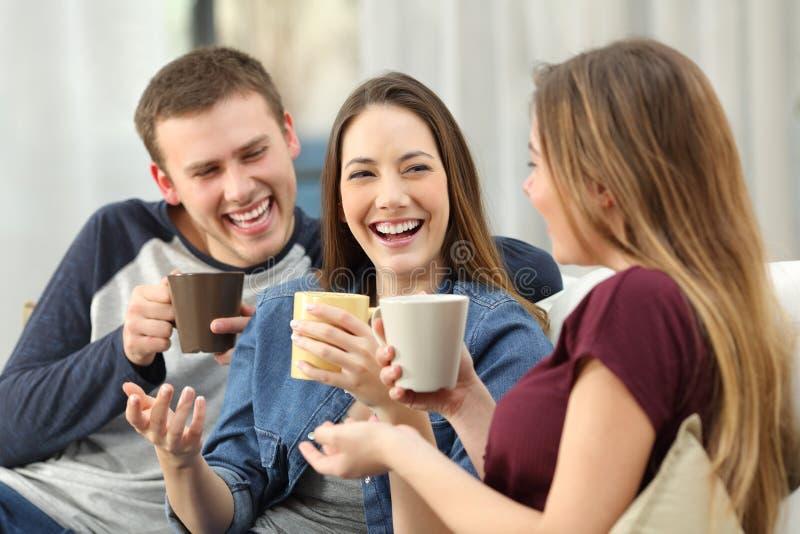 En luid vrienden die thuis spreken lachen stock fotografie