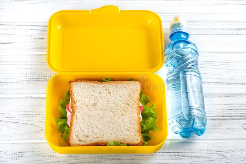 en lunchask med rostat bröd med skinka och grönsallat och ett plast- flaskvatten på en vit trätabell är arkivbild