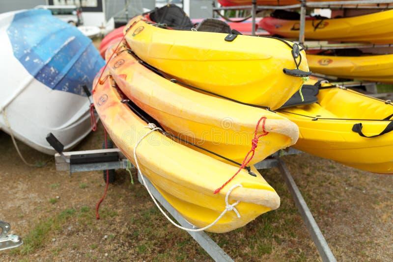 En luz del sol, los kajaks del rojo, amarillos y blancos colocaron al revés en los estantes del almacenamiento del metal Canoa al foto de archivo