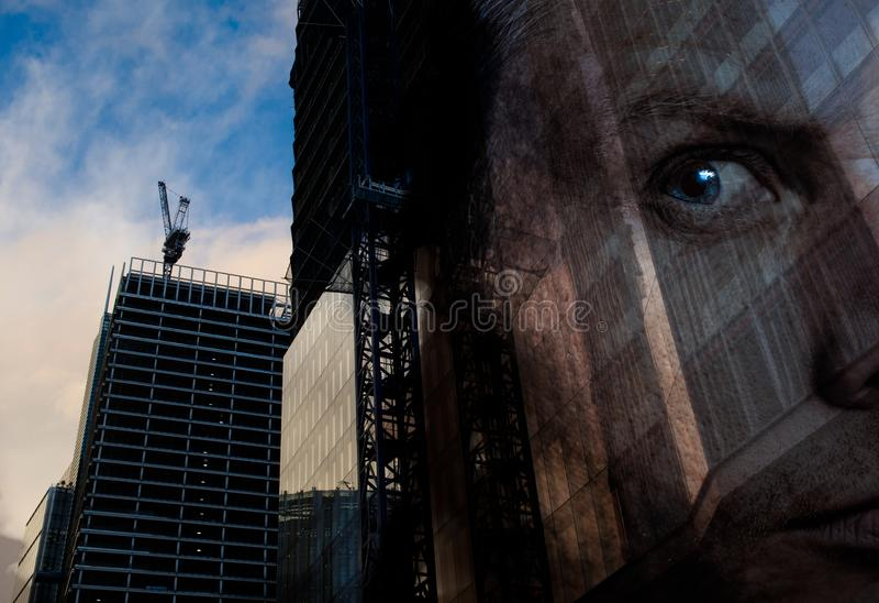 En lyckad affärsman ser över konstruktion av nya industribyggnader Dubbel exponering av manframsidan över kommersiellt kontor royaltyfri fotografi