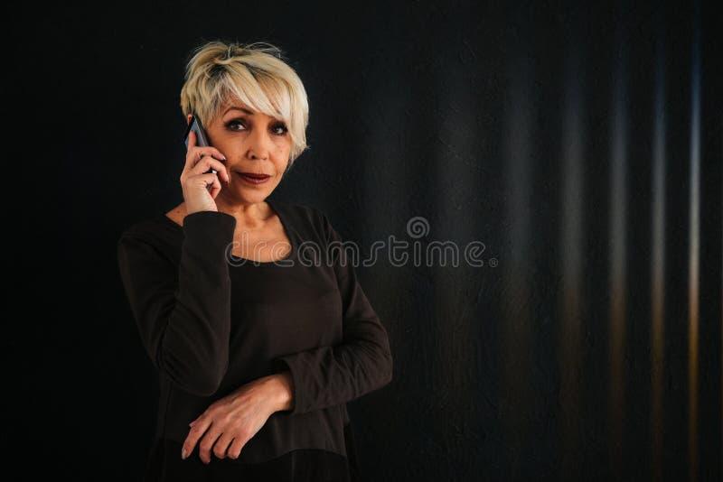En lyckad positiv äldre kvinnlig konsulent förhandlar en mobiltelefon Kommunikation mellan att använda för folk som är modernt arkivbild