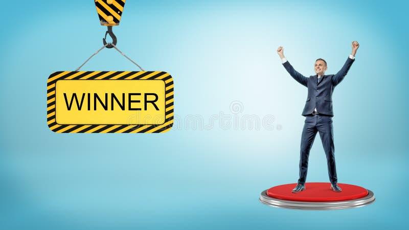 En lycklig affärsman står på en röd tryckknapp nära en läs- vinnare för konstruktionstecken royaltyfri foto