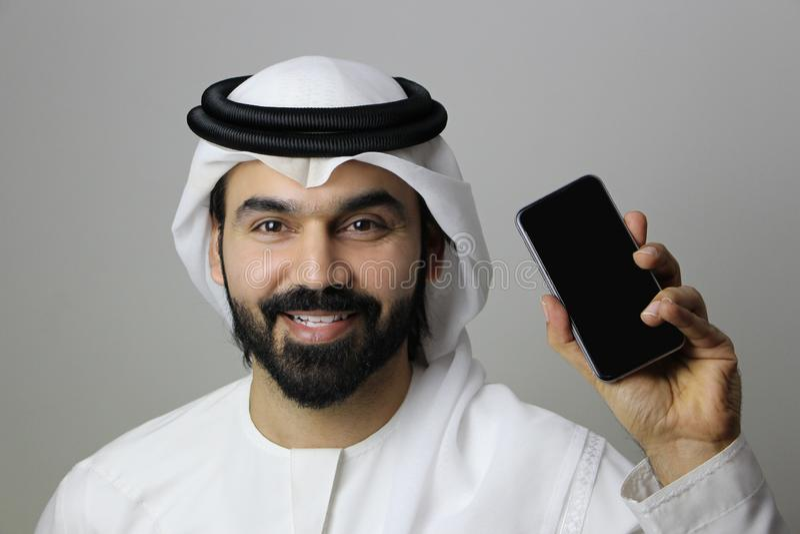 En lycklig arabisk man som rymmer en mobiltelefon arkivbilder