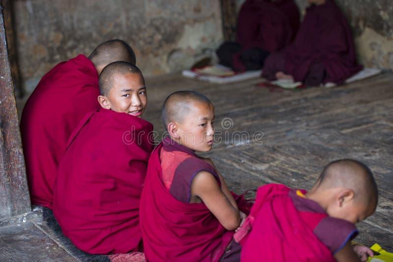 En lycklig bhutanesisk ung novismunk att vända hans huvud för att le när under studien, Bhutan arkivbild