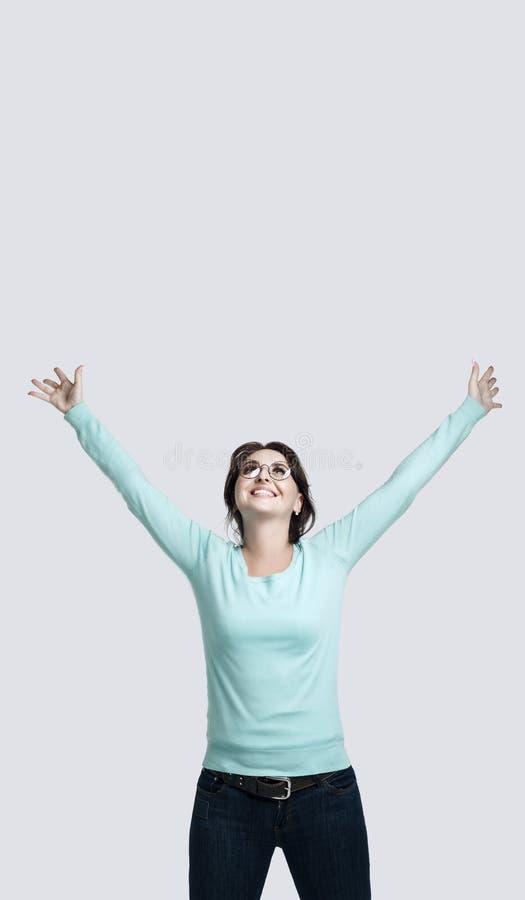 En lycklig brunettflicka i ettfärgat förkläde står mot den gråa bakgrunden som den unga kvinnan lyftte hennes händer upp leenden royaltyfri bild