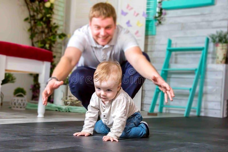 En lycklig fader som spelar med sonen Han försöker att fånga ett lyckligt barn att krypa på alla fours arkivfoto