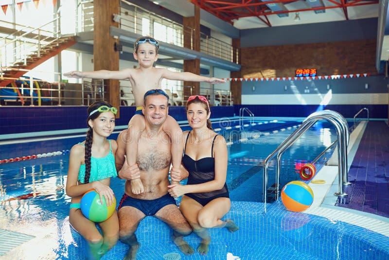 En lycklig familj i en simbassäng inomhus arkivfoto