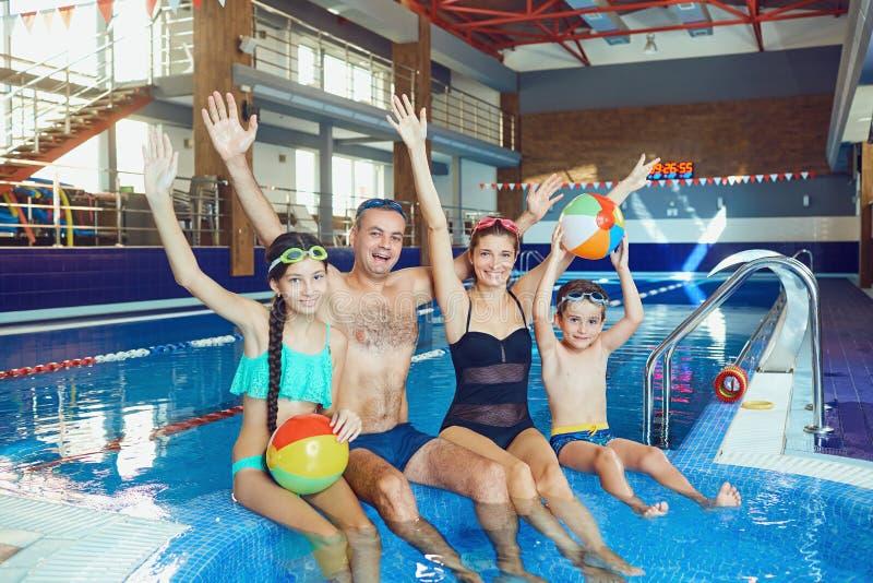 En lycklig familj i en simbassäng inomhus fotografering för bildbyråer