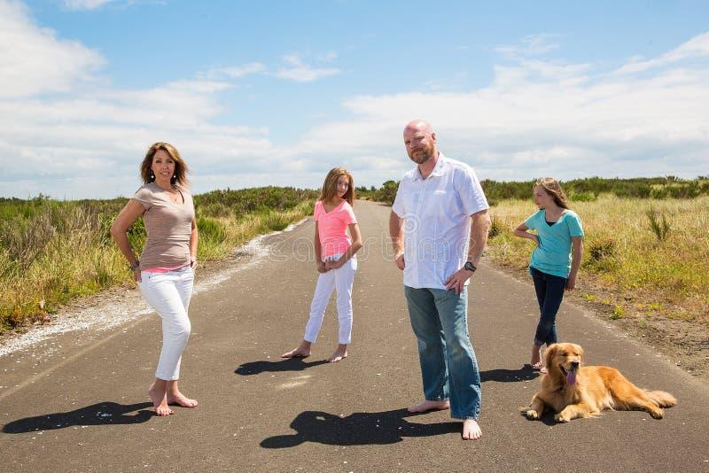 En lycklig familj på en tyst landsväg royaltyfri bild