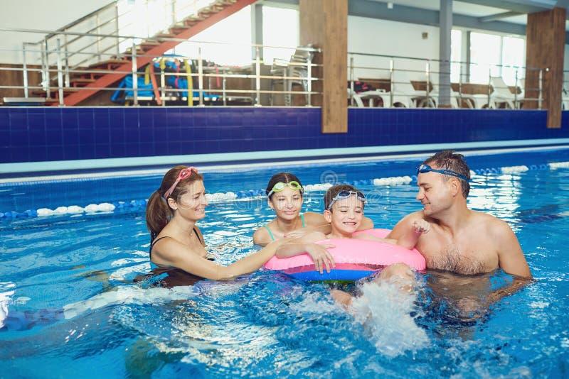En lycklig familj simmar i en simbass?ng inomhus royaltyfri bild