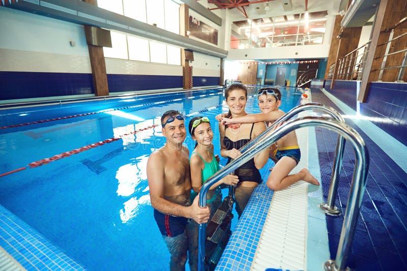 En lycklig familj skrattar i simbassängen fotografering för bildbyråer