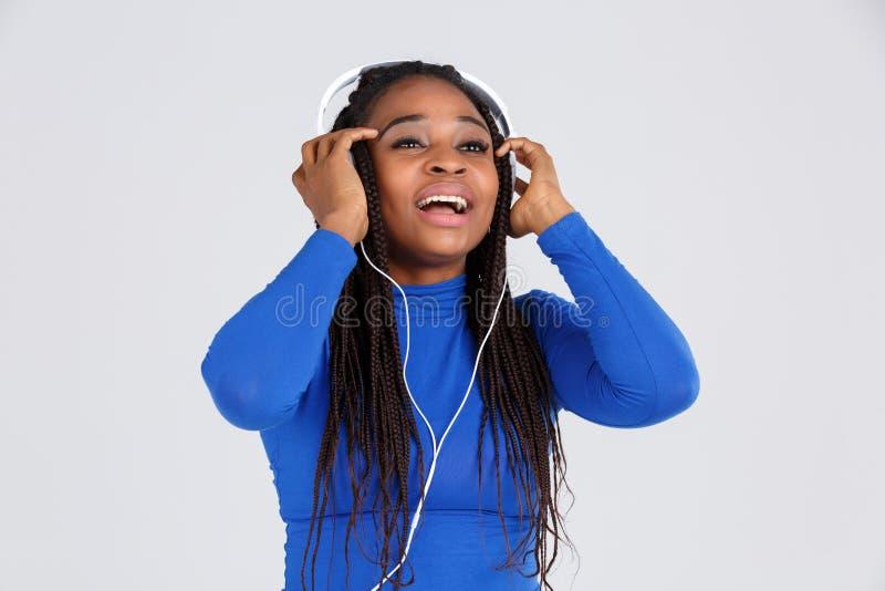 En lycklig flicka i hörlurar rymmer på till dem mot en grå bakgrund arkivbild