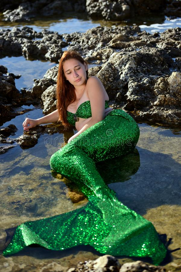 En lycklig flicka i en sjöjungfrudräkt ligger i vattnet bland stenarna på stranden och ser sjöjungfrusvansen royaltyfri fotografi