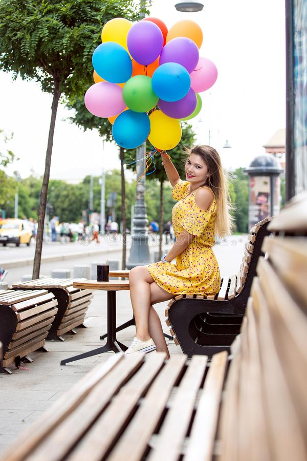 En lycklig flicka med ballons i hand arkivbild