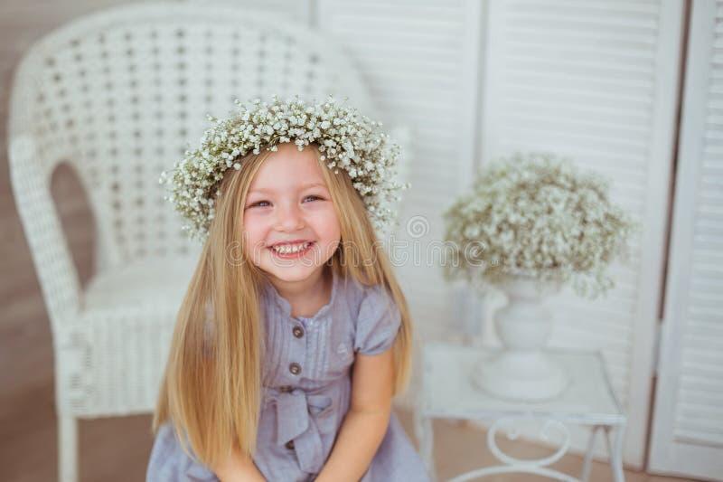 En lycklig flicka med en blom- krans grinar arkivbilder