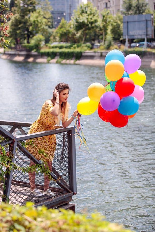 En lycklig flicka på floden med ballons i hand royaltyfri foto