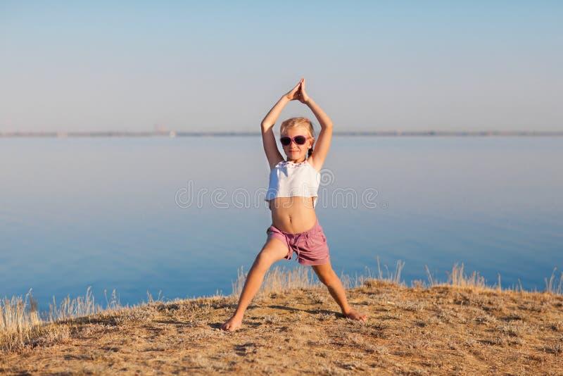 En lycklig flicka som utomhus gör yoga royaltyfria bilder