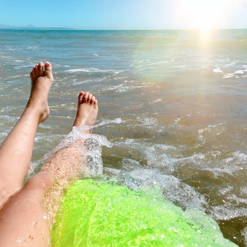 En lycklig flicka sparkar fot på ett hav, och plaska vatten på segla fartyget, sommartidferie royaltyfri bild