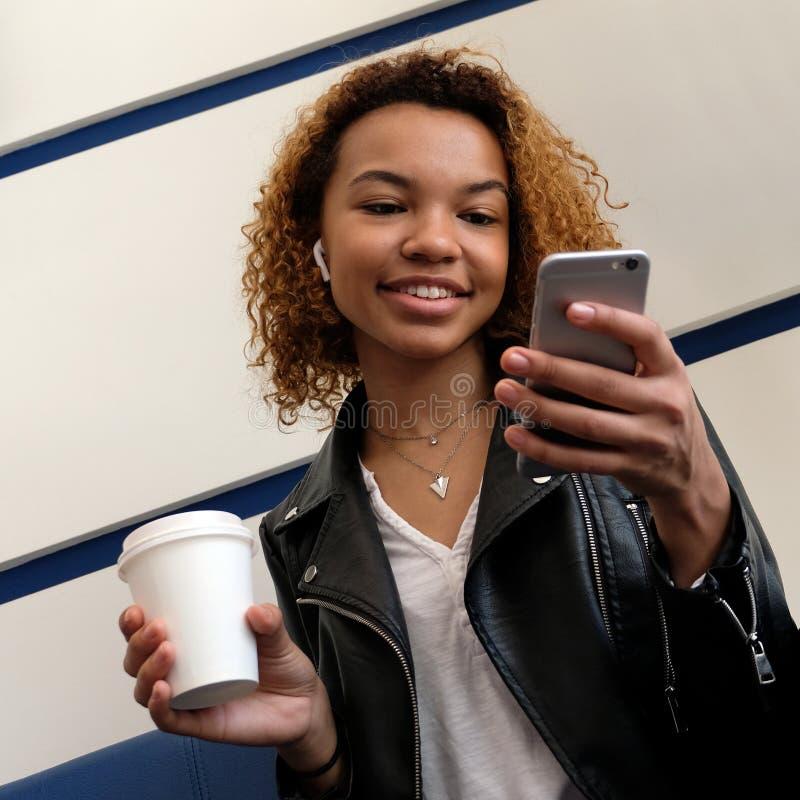 En lycklig härlig afrikansk amerikanflicka med en vit trådlös skalm i hennes öra ser in i telefonen, medan sitta i wen arkivbild