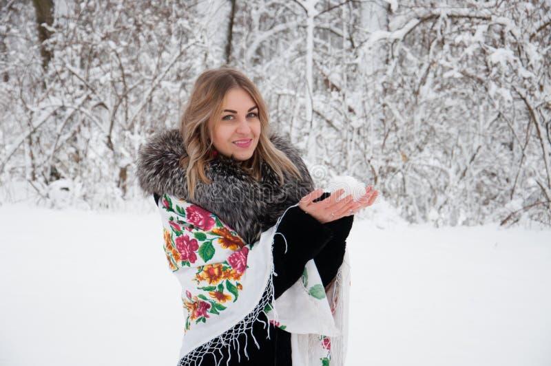 En lycklig kvinna går till och med vinterskogen, kastar snöboll skrattar tycker om lekar med, och liv arkivfoto