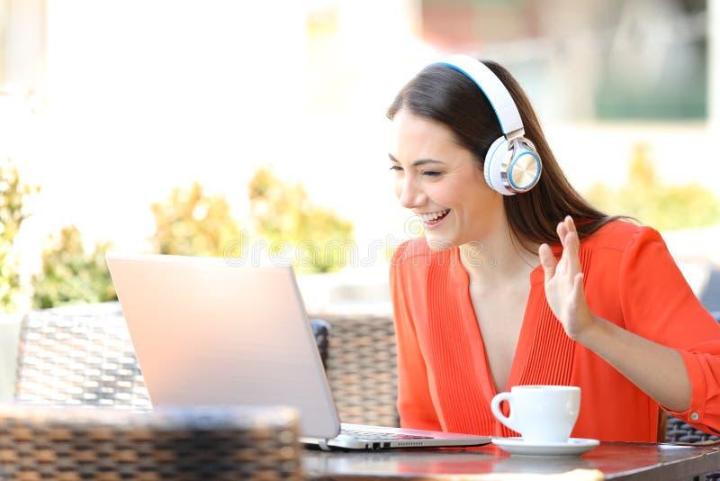 En lycklig kvinna som har ett videosamtal med en bärbar dator i en bar royaltyfri bild