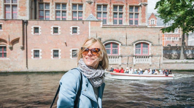 En lycklig kvinna står mot bakgrunden av typiska belgiska hus i Bruges, Belgien royaltyfri bild