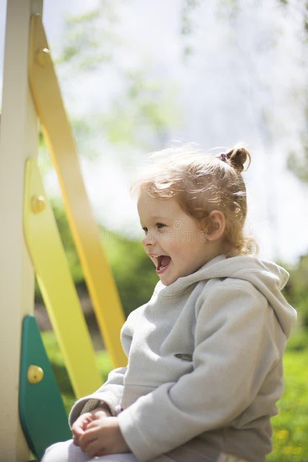 En lycklig liten flicka p? lekplatsen kl?ttrade p? barn en glidbana och b?rjade att skratta och fnissa royaltyfria bilder