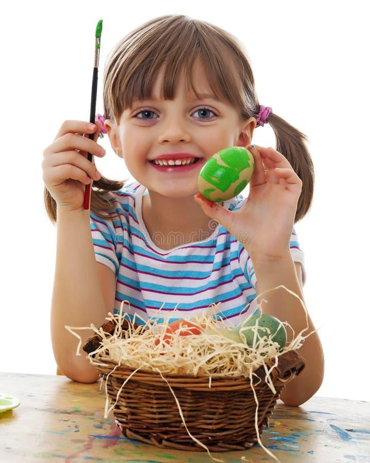 En lycklig liten flicka som målar easter ägg arkivbild