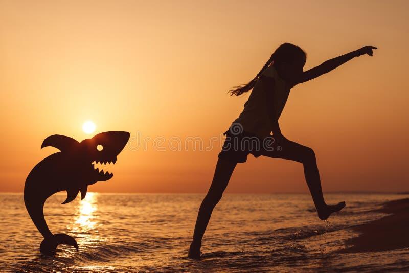 En lycklig liten flicka som spelar på stranden på solnedgångtiden royaltyfria bilder