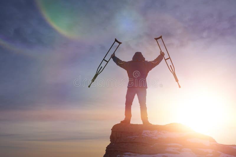 En lycklig man överst av ett berg med kryckor och att lyfta upp hans händer, mitt emot en dramatisk himmel på gryning arkivfoton