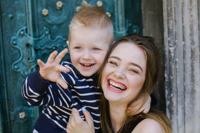 En lycklig moder kramar hennes lilla son skratt Begrepp av förälskelse, familjen, uppfostran och livsstilen arkivfoton