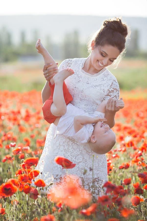 En lycklig moder med en liten son i hennes armar på det ändlösa fältet av röda vallmo på en solig sommardag fotografering för bildbyråer