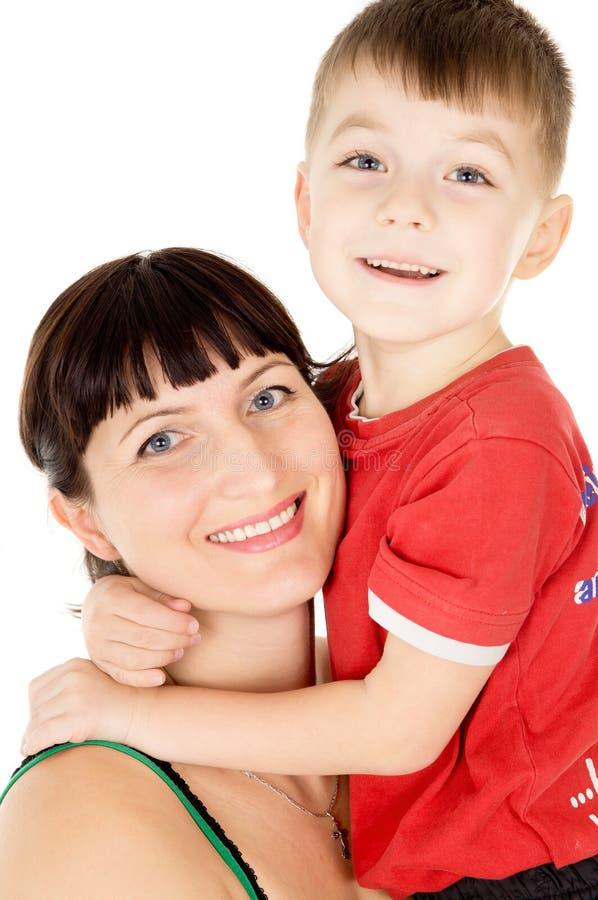 En lycklig moder omfamnar hennes barn arkivfoto