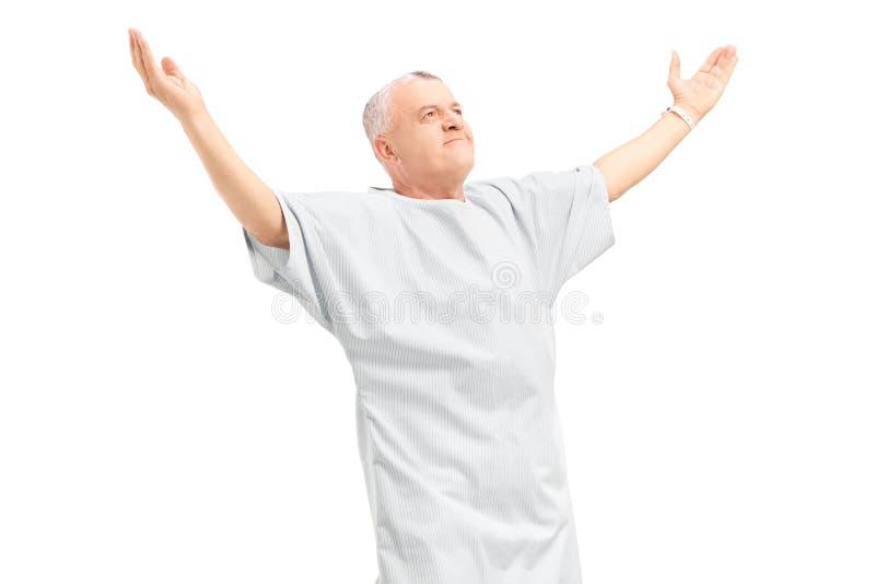 En lycklig mogen tålmodig som gör en gest lycka med lyftta händer arkivfoto