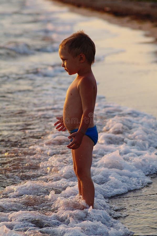 En lycklig pojke spelar i vågorna på stranden Gladlynta pojkebad i havet vinkar på solnedgången arkivbilder