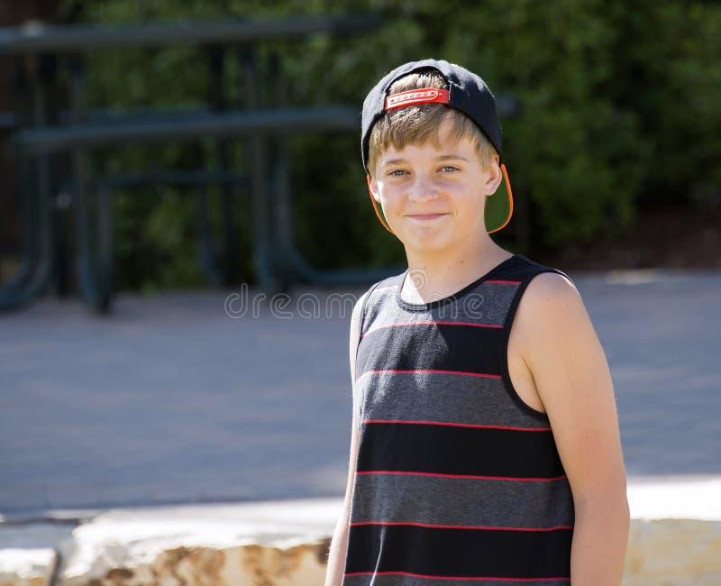 En lycklig tonårs- pojke i ett lock ler för en stående royaltyfria bilder