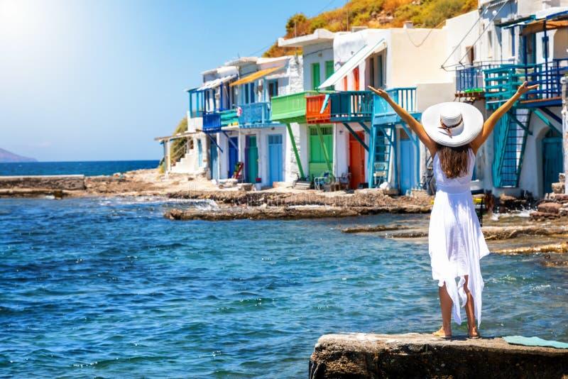 En lycklig turist i vit klänning har samma syn på fiskesammen Klima, Milos, Grekland royaltyfri bild