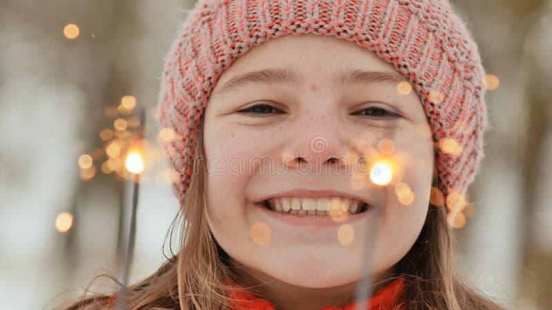 En lycklig ung skolflicka med mousserande gnistor av bengal ljus bland närbilden för vinterskogframsida På helgdagsaftonen av fotografering för bildbyråer
