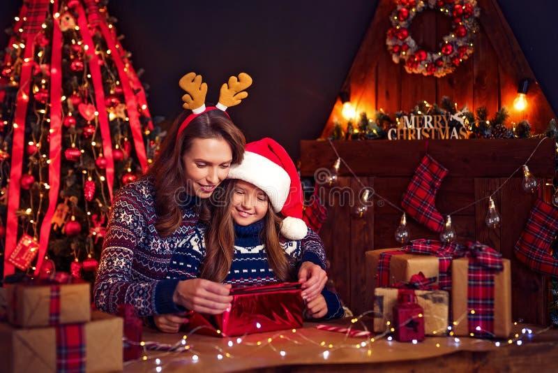 En lyckligt familjmoder och barn packar julgåvor arkivbilder