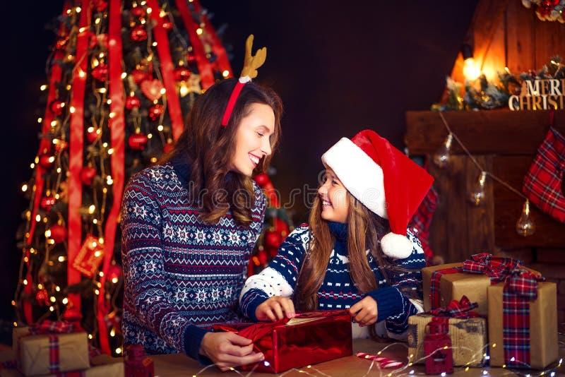 En lyckligt familjmoder och barn packar julgåvor arkivfoton