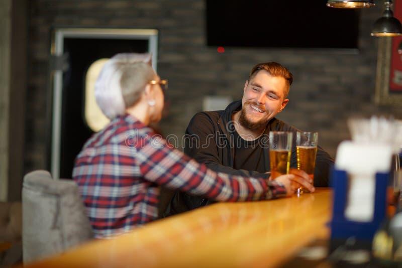 En lyckligt grabb, sammanträde och samtal i en stång med en flicka och att dricka öl och att skratta inomhus arkivbild
