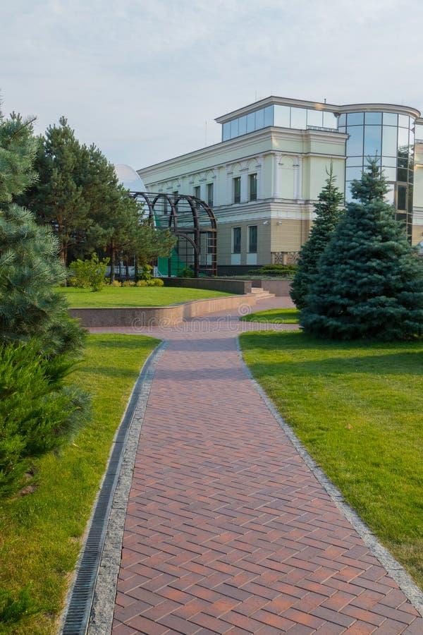 En lyxig gräsmatta i parkera och en slingrig bana dem emellan till byggnaden arkivfoton