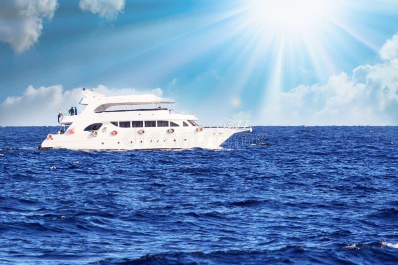 En lyxig privat motorisk yacht under väg på det tropiska havet med pilbågevågen Utrymme för text arkivbild