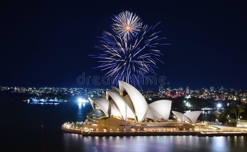 En mäktig skärm av fyrverkerier tänder upp himlen i blått och vit över Sydney Opera House royaltyfri bild