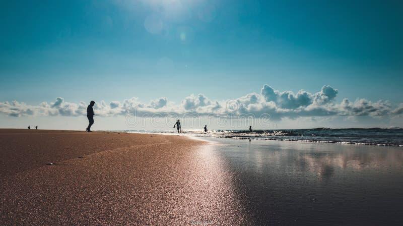 En människas bakgrundsbelysta silhuett nära marken pÃ¥ en soltropisk morgon pÃ¥ havsstranden fotografering för bildbyråer