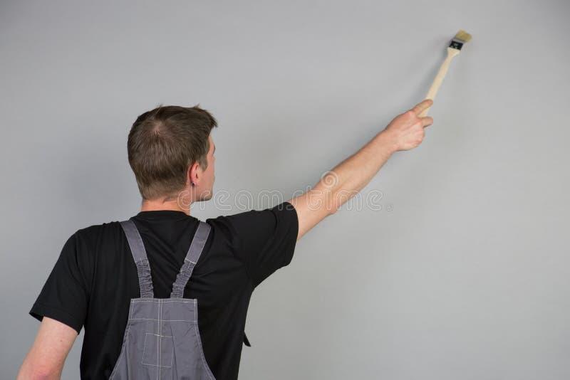 En målare använder en borste över hans huvud för att måla väggen royaltyfria foton