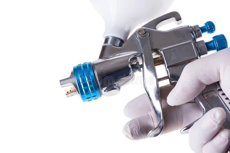 En målares armhand som rymmer den industriella formatsprutpistolen använd för arkivbilder